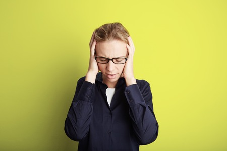 Portrait Handsome Pretty Young Woman Who Grabs Her Head Hands Headache.Empty Yellow Background.Beauty,Shock,Fashion People Photo.Girl Wearing Glasses Closed Eyes Camera Studio Shot.Horizontal Image Stock Photo