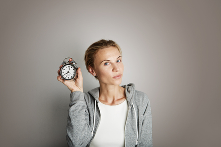 Portrait Handsome Young Woman Posing Blank Gray Background.Pretty Girl Smiling Holding Vintage Alarm Clock Hand Empty Wall.Beauty Lifestyle Fashion Hipster People.Casual Time Abstract Concept