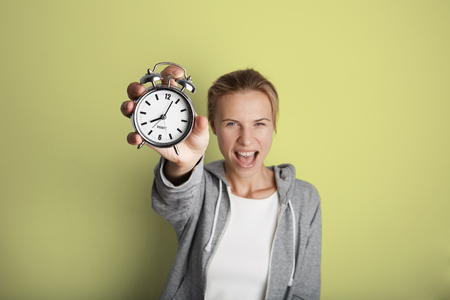 Portrait Handsome Young Woman Posing Blank Yellow Background.Pretty Girl Screaming Holding Vintage Alarm Clock Hand Empty Wall.Beauty Lifestyle Fashion Hipster People.Wake Up Time Abstract Concept