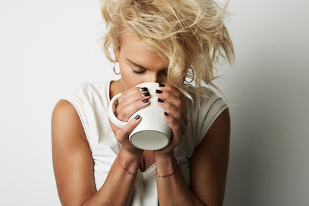 Portrait Young Blonde Head Female Perfect Skin Holding Hands White Cup Copy Space Wall Your Business Information or Advertising Content.Girl Drinking Hot Coffee Studio Shoot