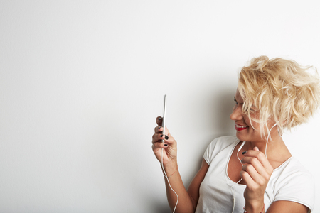 Stylish Female Making Selfie or Cheking Email via Smartphone While Standing Against White Background and Listening Music Earphones.Copy Space Your Business Text Message Promotional Content