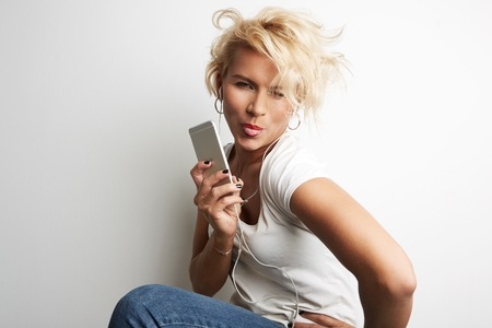 Stylish Female Making Selfie Smartphone While Standing Against White Background Listening Music Earphones.Copy Space Your Business Text Message Promotional Content.Young Girl Smiling Showing Tongue Stock Photo