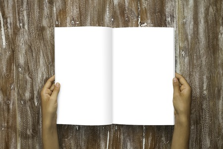 Closeup Blank Open Book White Paper Sheet Holding Male Hands. Mockup Natural Wood Table Background. Empty Mock up Painted Brown Desk