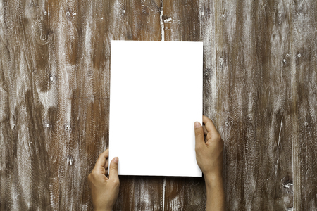 Closeup Blank White Paper Sheet Mockup Holding Male Hands Natural Wood Table Background. Empty Canvas Painted Brown Desk