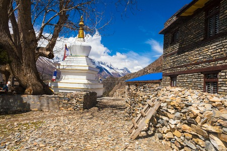 Tibetan prayer stupa or prayers place of the faithful Buddhists in center Mountains Village. Blue Sky Background. Horizontal photo