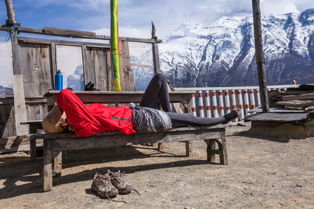Beautiful Woman Traveler Backpacker Take Rest Mountain Terrace Village.Young Girl Sleeping Bench.North Snow Peaks Landscape Background. Cloudy Sky Stock Photo - 63727329