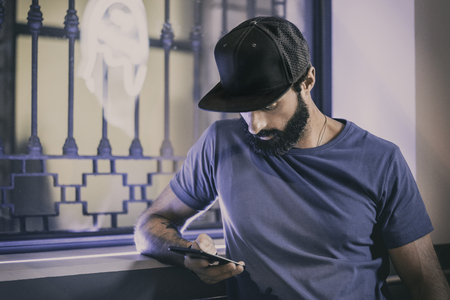 Young bearded man sitting in cafe and using smartphone for texting message. Horizontal. Blurred background