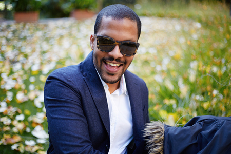 Portrait of Happy confident young African-American businessman in formal wear and sunglasses sitting at city park