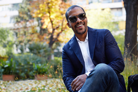 Portrait of Happy confident young African-American businessman in formal wear and sunglasses sitting at city park.Blurred background