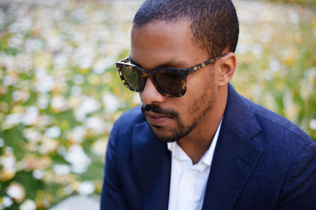 Closeup Portrait of Happy confident young African-American businessman in formal wear and sunglasses sitting at city park Stock Photo