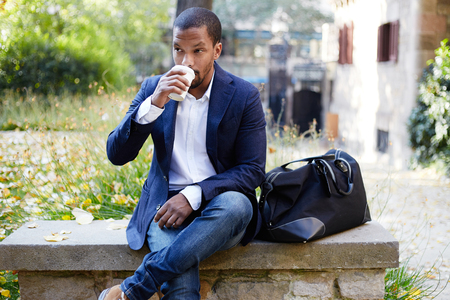 Portrait of smiling confident young African-American businessman in formal wear sitting at bench in city park and drinking hot coffee.Blurred background.Horizontal Stock Photo