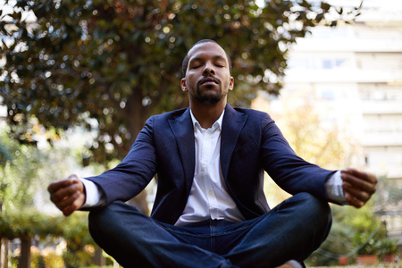 Young american african businessman in informal clothes meditating in lotus pose taking a deep breath outside corporate office.Business yoga and stress free environment.Peace of mind concept.Blurred Stock Photo