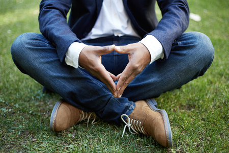 Young american african businessman in formal wear meditating in lotus pose taking a deep breath outside corporate office.Business yoga and stress free environment.Peace of mind concept.Blurred Stock Photo