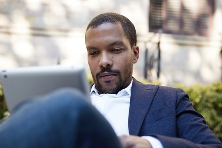 Pensive american african businessman in informal clothes working at sunny street on electronic touch pad,checking e-mail using Internet-enabled electronic device,calling friends via social networks Stock Photo