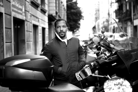 Black and white Portrait of Happy confident young African-American hipster in formal wear and sunglasses at city front of moto bikes.Blurred background