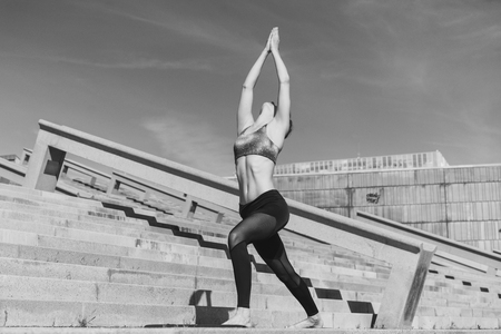 Fitness woman concept. Yoga and meditation in a modern urbanistic city. Young attractive girl - yoga meditates against modern skyscrapers. Black and white. Stock Photo
