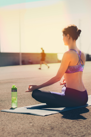 Fitness woman concept. Yoga and meditation in a modern urbanistic city. Young attractive girl - yoga meditates against modern skyscrapers. Vertical Stock Photo