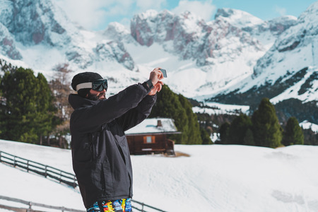 Bearded young snowboarded in sunglass mask, at the ski resort on the background of mountains and blue sky.Man making selfie photo on his smart phone. Horizontal.Blurred background