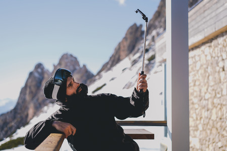 Bearded handsome snowboarded in sunglass mask making selfie on smartphone at the ski resort. Blurred mountains and blue sky on the background.Horizontal image.