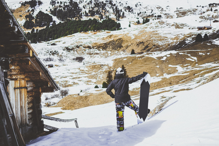 Snowboarder wearing black jacket, mask with snowboard close authentic wooden house.Man looking at panoramic mountans view. Horizontal