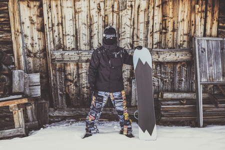 Snowboarder wearing black jacket, mask with snowboard close authentic wooden house. Horizontal