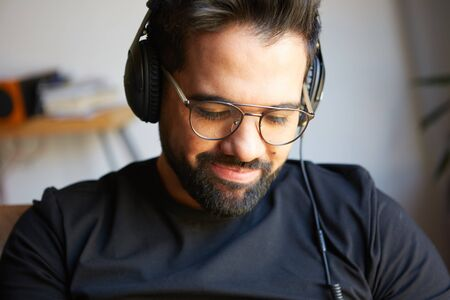 Portrait of handsome bearded man in headphones listening to music at home. Relaxing and rest time concept. Blurred background