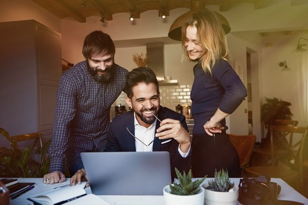 Group of three young coworkers discussing new ideas at modern apartment, using mobile laptop computer. Horizontal, blurred background.Blurred background