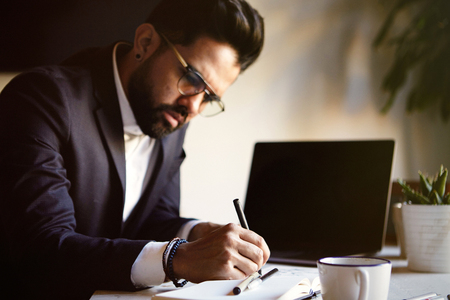 Closeup portrait Young bearded man working at living room at home. Man writing notes and using electronic gadget. Blurred background. Stock Photo