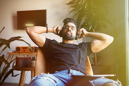Smiling bearded man in headphones enjoing listening to music on tablet at home. Relaxing and rest time concept. Blurred background