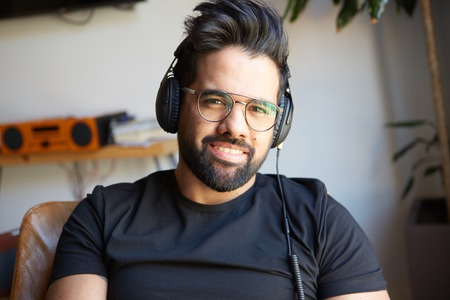 Portrait of Smiling bearded man in headphones enjoing listening to music on at home. Relaxing and rest time concept. Blurred background Stock Photo