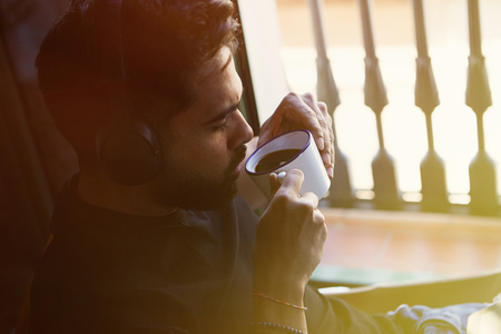 Handsome bearded man in headphones listening to music and enkoing cup of coffee at home. Casual relaxing and rest time concept. Blurred background