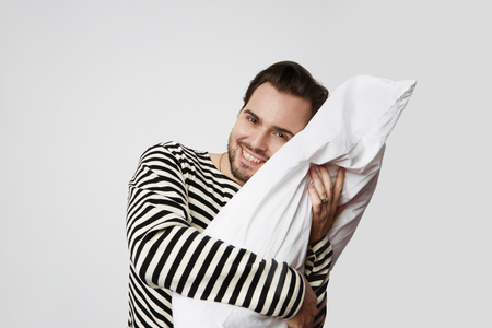 Smiling handsome man with white soft pillow on empty background. Studio shoot. Horizontal Stock Photo