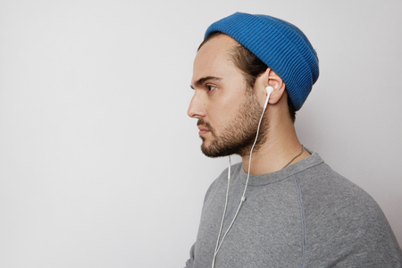 Handsome young man listening to music on headphones over empty light empty background at studio. Horizontal
