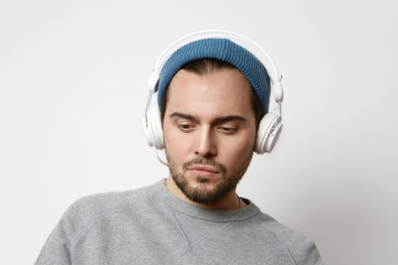 Portrait of Pensive young man listening to music on headphones over empty light background at studio. Horizontal