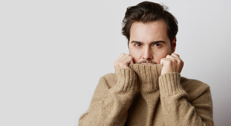 Portrait of young fashion model in pullover sweater poising while standing on white background. Horizontal
