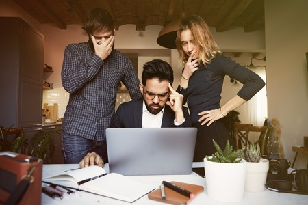 Three young coworkers working at modern studio on mobile laptop computer. Horizontal, blurred background.Visual effects Stock Photo