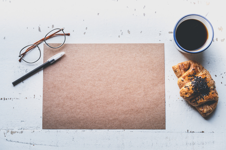 Creative work concept.Business background for letter writing.Mock-up blank craft sheet of empty paper, pen, eye glasses and morning coffee cup with croissant on white wooden desk Stock Photo