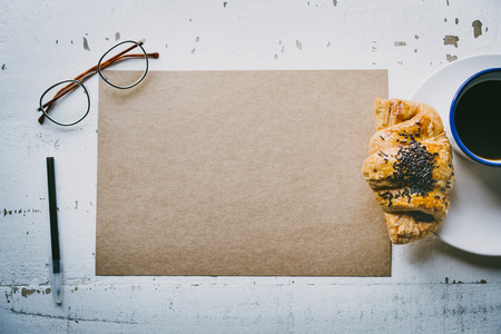 Mock-up blank craft sheet of empty paper, pen, eye glasses and morning coffee cup with croissant on white wooden desk. Business background for letter writing.Creative work concept