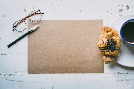 Business background for letter writing.Mock-up blank craft sheet of empty paper, pen, eye glasses and morning coffee cup with croissant on white wooden desk. Creative work concept