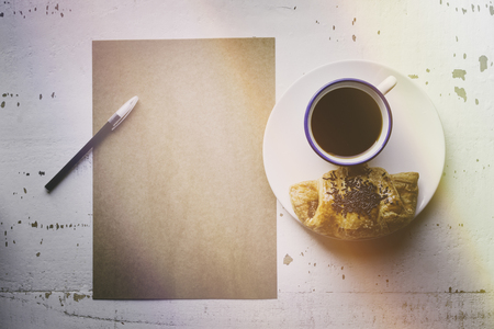 Mockup blank craft sheet of blank craft paper, pen, eye glasses and morning coffee cup with croissant on white wooden desk. Business mock-up background for message writing.Creative work concept.Flares