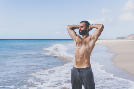 Workout exercise concept.Healthy Handsome Active Man With Fit Muscular Body enjoing sun on the beach at the morning. Sporty Athletic Male Exercising At Beach. Training Outdoor. Sports And Fitness
