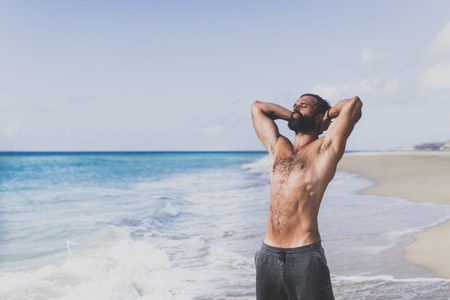 Workout exercise concept.Healthy Handsome Active Man With Fit Muscular Body dreaming on the beach at the morning. Sporty Athletic Male Exercising At Beach. Training Outdoor. Sports And Fitness