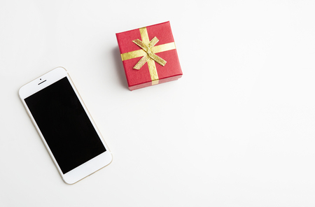 Mockup of smartphone, gift box on empty white clean desk. Business mock-up background for message writing.Top view. Horizontal Archivio Fotografico