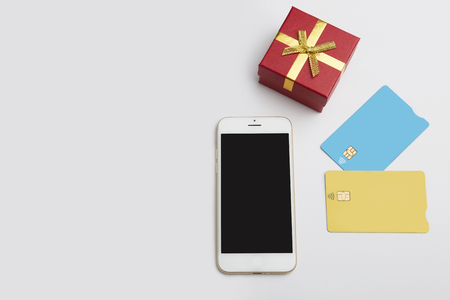 Mockup of two blank color credit cards, smartphone, gift box on empty clear desk. Business mock-up background for message writing.Top view. Horizontal