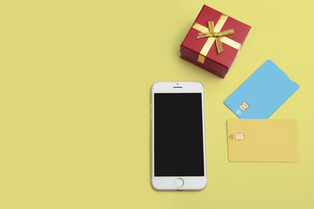 Mockup of two blank color credit cards, smartphone, gift box on empty yellow desk. Business mock-up background for message writing.Top view. Horizontal Stock Photo