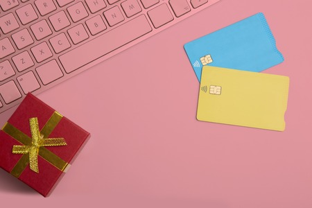 Mockup of two blank color credit cards, gift box on empty pink desk background. Business mock-up background for message writing.Top view. Horizontal