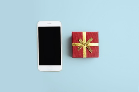 Mockup of smartphone, gift box on empty blue clean desk. Business mock-up background for message writing.Top view. Horizontal Stock Photo - 101125212