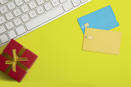 Mockup of two blank color credit cards, gift box on empty yellow desk. Business mock-up background for message writing.Top view. Horizontal