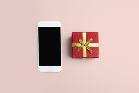 Mockup of smartphone, gift box on empty clean desk. Business mock-up background for message writing.Top view. Horizontal