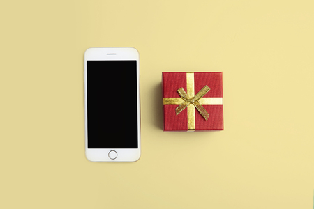 Mockup of smartphone, gift box on empty yellow clean desk. Business mock-up background for message writing.Top view. Horizontal Stock Photo - 101125216